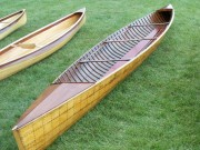 "Peterbourough Racer Canoe - image 3 of 3 Peterborough Canoe Co. ""Racer"" 17 ft. all-wood canoe built in early 1900's in Peterborough, Ont. Found in Shoreham, VT and restored in 2008. Two paddlers in upright position with one knee on the floor one foot on the floor. Work included new gunwales, decks and deck framing, planking and stem repairs, new thwart, stripping and varnishing."
